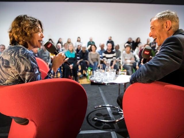 Zwei Menschen sitzen auf Stühlen und beantworten Fragen