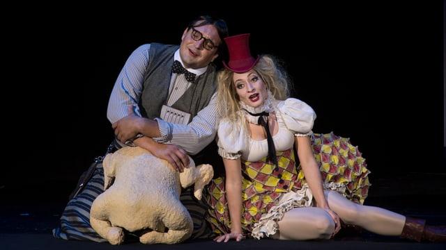 Papageno und Pamina sitzen auf dem Boden. Sie tragen zirkusähnliche Kostüme.
