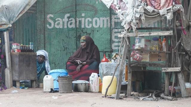 Frau sitzt vor einer Hütte im Flüchtlingslager Dadaab in Kenia.