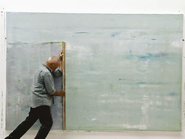 Richter schabt mit einem Brett die Farbe von einem grosse, abstrakten Gemälde.