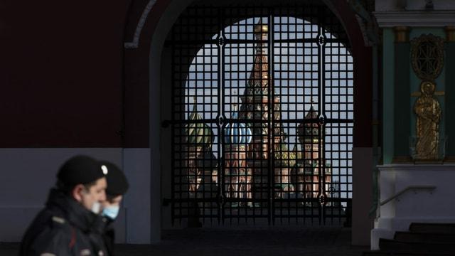 Polizisten mit Gesichtsmasken patrouillieren in Moskau vor dem Auferstehungstor mit der Basilius-Kathedrale im Hintergrund.