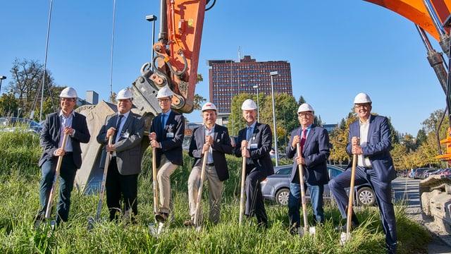 7 Männer mit Schaufeln und Bauhelmen vor einer Baggerschaufel
