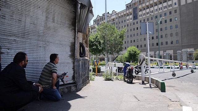 Zwei Männer, einer bewaffnet, beobachten das Parlamentsgebäude aus der Ferne.