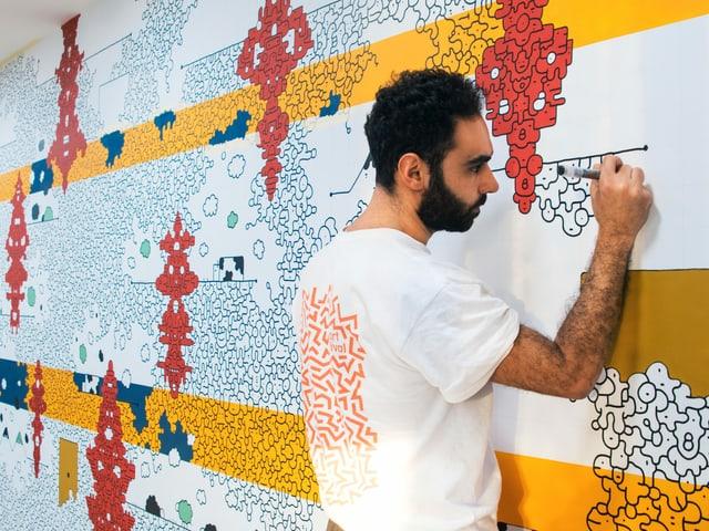 Ein Mann zeichnet an einer Wand.