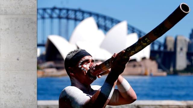 Aborigine mit Didgeridoo, im Hintergrund die Oper von Sidney.