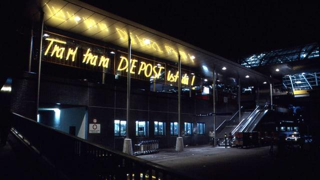Am Ende des Bahnhofplatzes Chur leuchtet gelb der Spruch «Tra ri tra ra DIE POST ist da».