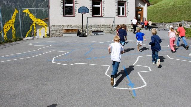 Kinder spielen Fangen auf einem Aussenplatz.