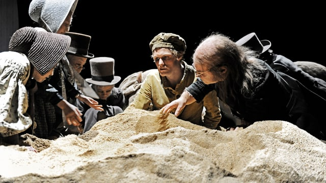 Schauspieler wühlen im Sand.