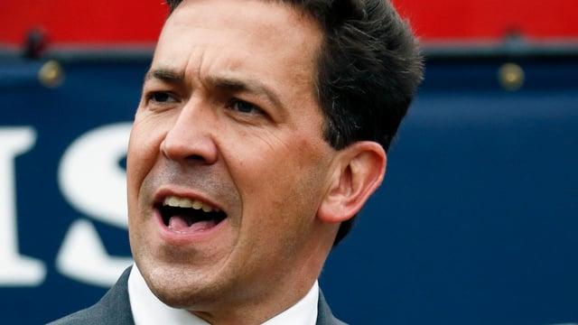 Ein Mann mit dunklen Haaren, Anzug und offenem Mund, er runzelt die Stirm und scheint gerade zu sprechen. Es ist ein Portrait, und der Mann ist Politiker.