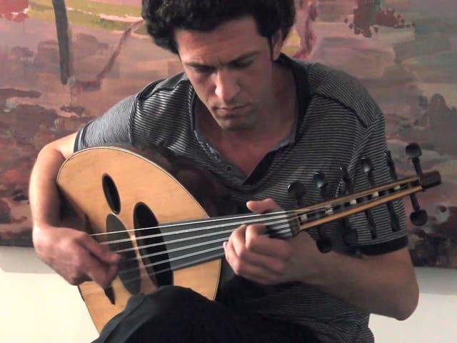 Der syrische Musiker Daisam Jalo spielt auf seinem Saiteninstrument.
