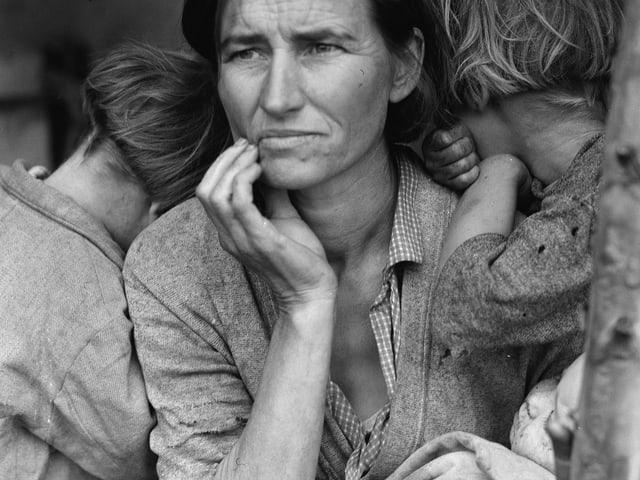Schwarzweissfoto einer Frau, die ein Säugling im Arm hält und melancholisch in die Ferne blickt – daneben drücken zwei Kinder ihre Gesichter an ihre Schultern.