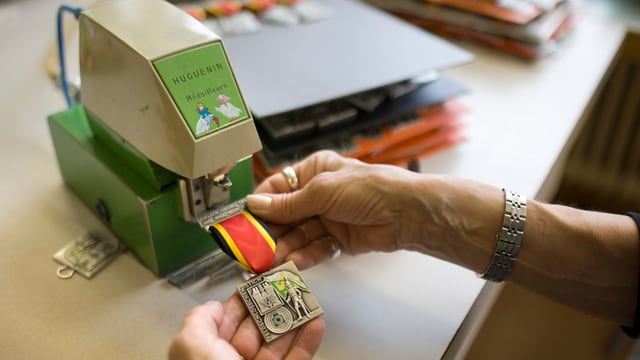 Ein Arbeiter (nur die Hände sichtbar) prägt ein Abzeichen für ein Feldschiessen.
