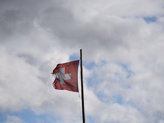 Eine beschädigte Schweizer Flagge vor dem bewölkten Himmel in Langnau im Emmental.