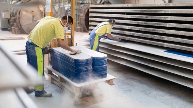 Zwei Mitarbeiter in einer Fabrikhalle bei Schleifarbeiten.