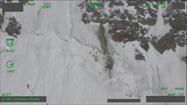 Luftaufnahme vom Absturzort zeigt Felsen und Schnee in steielem Gelände sowie ein rotes Wrackteil