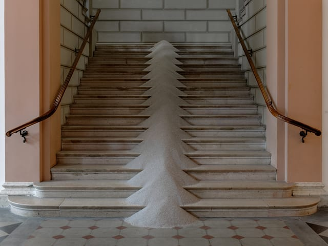 Eine Treppe, in deren Mitte Sand aufgehäuft ist.