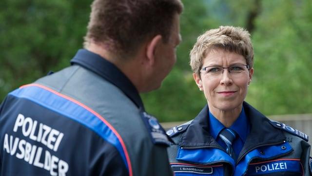 Frau in Polizeiuniform spricht mit Kollegen