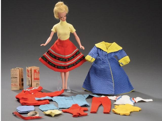 Spielzeugpuppe mi einer Auswahl an Kleidern.
