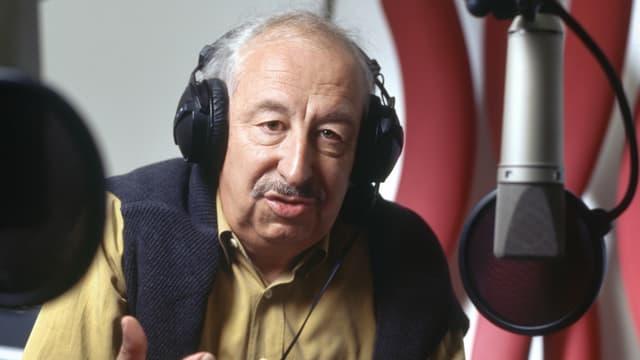 Rolnad Jeanneret, Mann mit Schnaz, mit Kopfhörer vor einem Radio-Mikrofon.