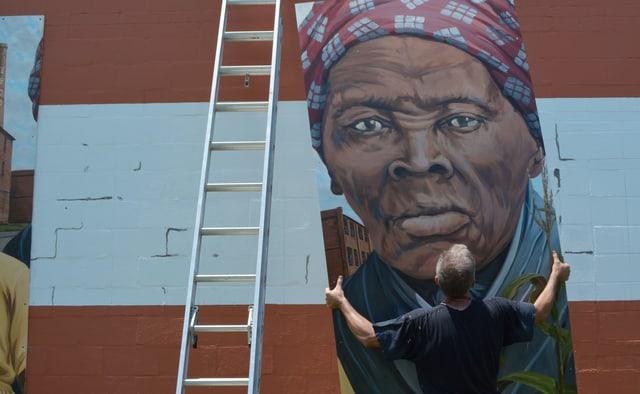 Jemand hängt ein Gemälde, das Harriet Taubman zeigt, an eine Wand.