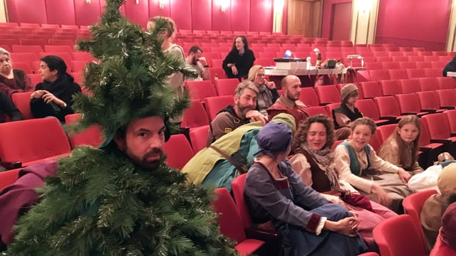 Ein als Tannenbaum verkleideter Mann sitzt im Zuschauerraum eines Theaters.