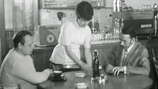 Schwarzweiss-Aufnahme: Eine Kellnerin bedient zwei Herren am Stammtisch.
