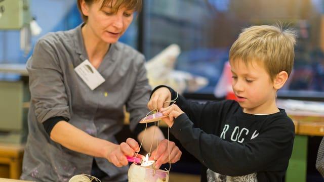 Eine Frau und ein Kind basteln an einem Räbenliechtli. Die Frau zündet eine Kerze an.