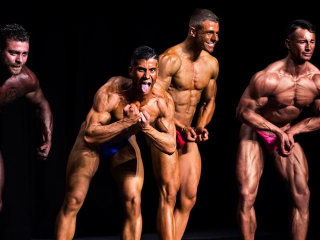 Bodybuilder verrenken sich und ziehen Grimassen.