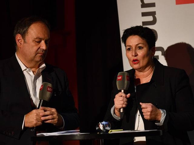 Zwei Personen mit Mikrophonen in der Hand.