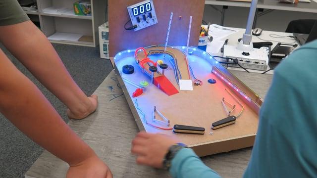 Kinderarme die einem leuchtenden Flipperkasten bauen.