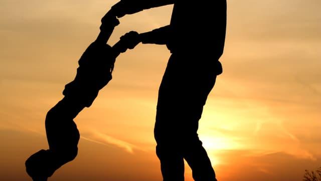 Kind an den Händen des Vaters hängend im Sonnenuntergang