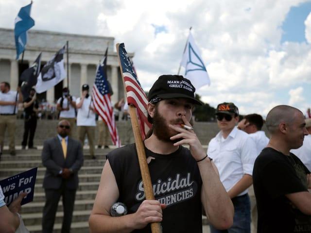 Ein junger Mann hält die amerikanische Flagge hoch, raucht eine Zigarette.