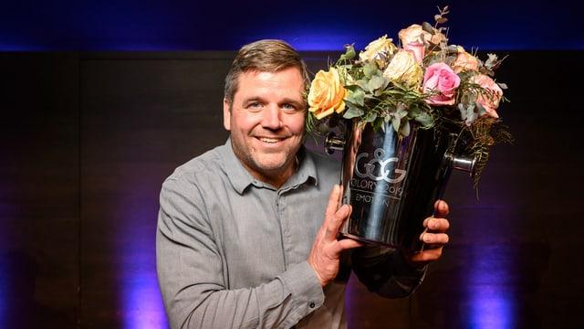 Mann in grauem Hemd mit Blumenstrauss in der linken Hand