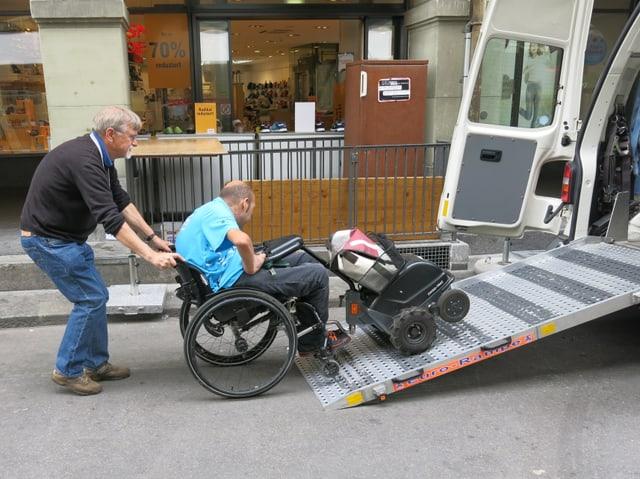 Ein Mann hilft einem Rollstuhlfahrer.