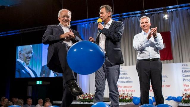 Johann Schneider-Ammann, Philipp Müller und Didier Burkhalter auf der Bühne. Schneider-Ammann kickt einen blauen Ballon weg.