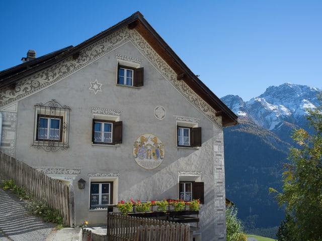 Hausfassade verziert mit Ornamenten im Engadiner Stil.