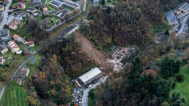 Luftaufnahme, der abgerutschte Hang ist deutlich zu sehen, unterhalg und oberhalb davon besiedeltes Gebiet und Strassen.