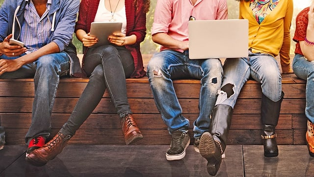 Jugendliche mit Smartphone, Tablet und Laptop