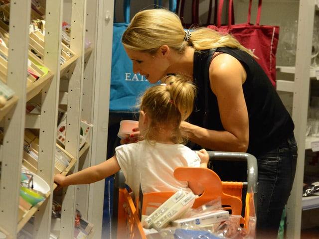 Michelle und Sole stehen vor einem Gestell und suchen etwas. Dabei ist Michelle etwas nach vorne gebückt und Sole sitzt im Einkaufswagen.