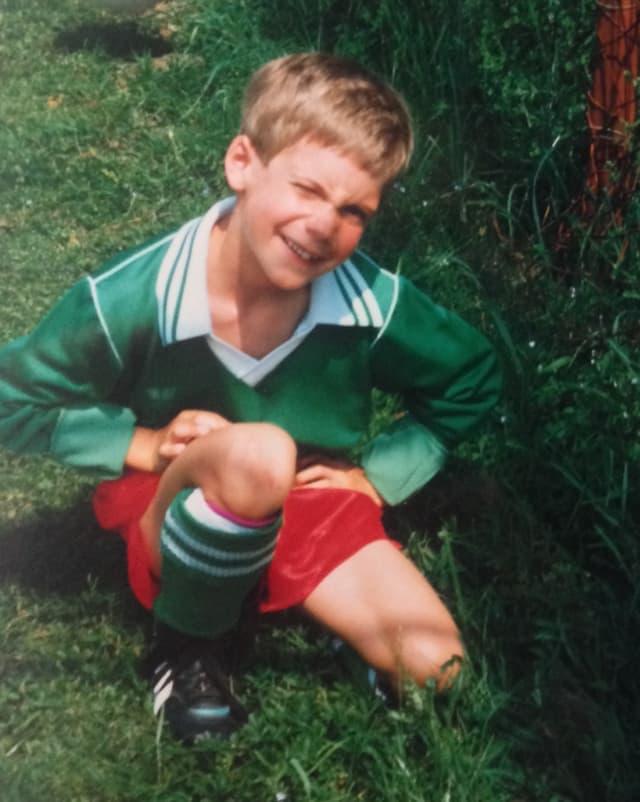 Ein kleiner Junge in grünem Fussballleibchen und roten Hosen.