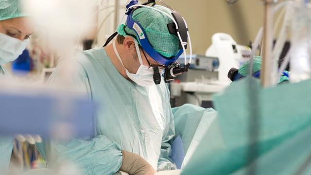 Ein Arzt operiert im Operationssaal.
