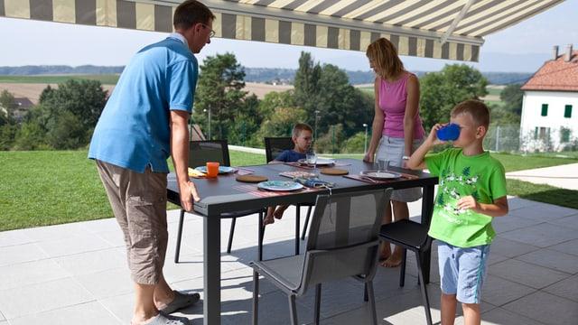 Junge Familie mit Küchentisch auf Sitzplatz