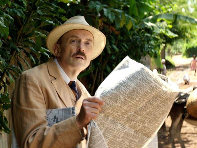 Mann mit Hut und einer Zeitung vor einem üpiigen, exotischen Wald.
