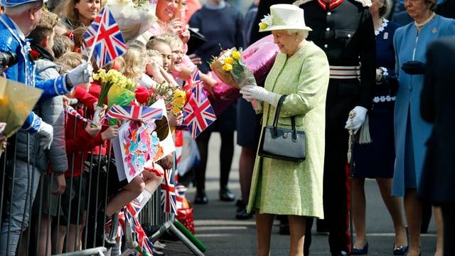 .Die QUeen in einen gelben Matel mit passendem Hut. Sie nmmt Blumen aus der feiernden Menge entgegen