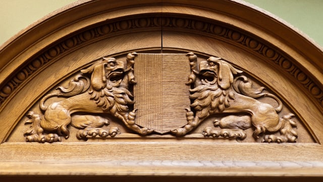 Emblem aus Holz im Nationalratssaal mit dem Tessiner Wappen.