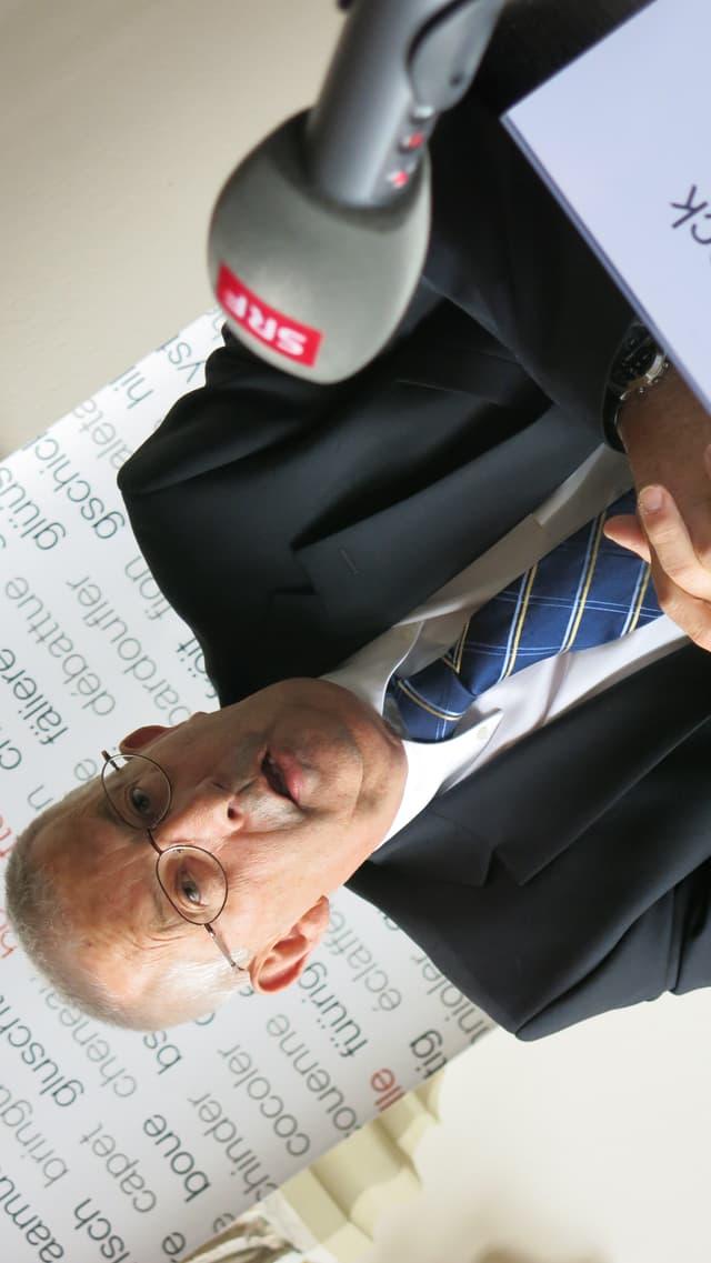 Ein Mann mit Brille sitzt vor einem Mikrofon.