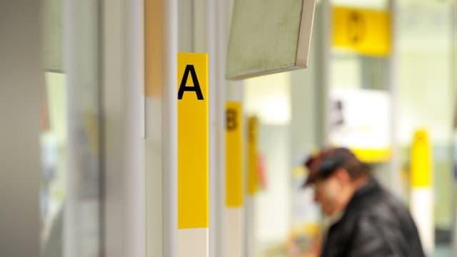 Mann an einem Postschalter