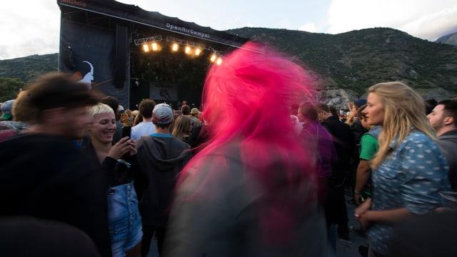 Menschen vor der Bühne am Openair Gampel, jemand in der Mitte hat pinkfarbene Haare.