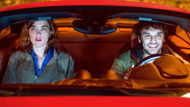 Mann und Frau in einem roten Auto