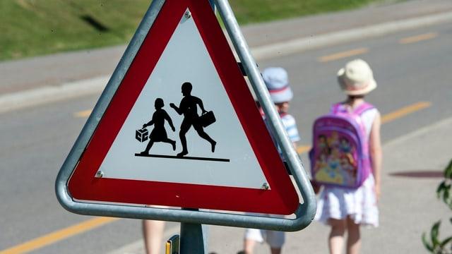 """Ein """"Achtung Schule"""" Schild, dahinter zwei Kinder mit Thek."""